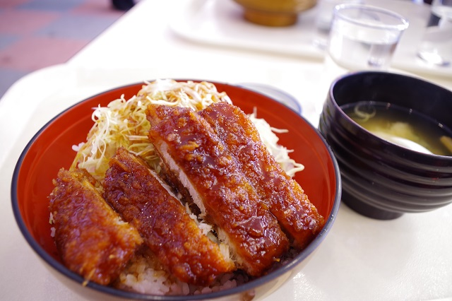 Glazed pieces of fried pork cutlet on a bed of rice in a red and black bowl. Behind it are a glass of water and miso soup.